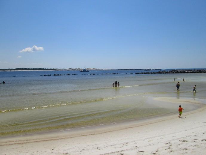Calm shallows on the beach behind the jetty