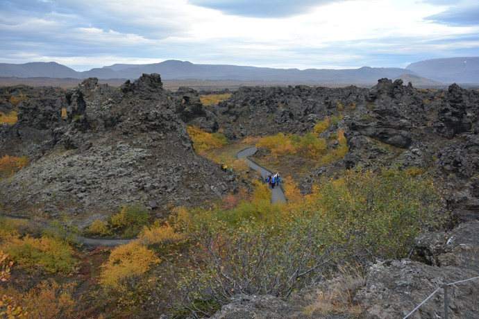 Watching John and fellow travelers hike in the lava maze at Dimmuborgir